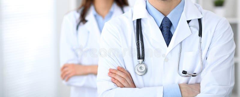 站立直接在医院办公室的未知的医生Groupe  关闭听诊器在实习者乳房 免版税图库摄影