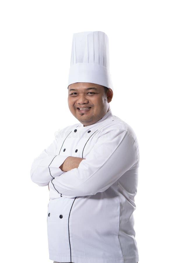 站立确信的横渡的手的年轻男性厨师画象摆在神色在照相机的前面 库存照片