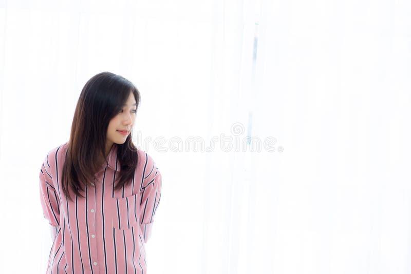 站立窗口的美丽的年轻亚裔妇女画象和微笑,当醒与日出在早晨时 库存照片