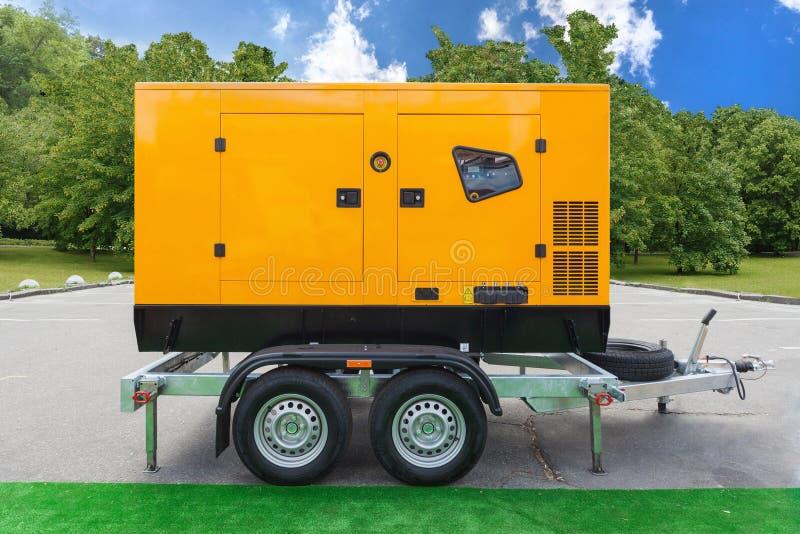 站立紧急的电力的流动柴油充电发电器外部反对绿色树和天空蔚蓝 免版税库存图片