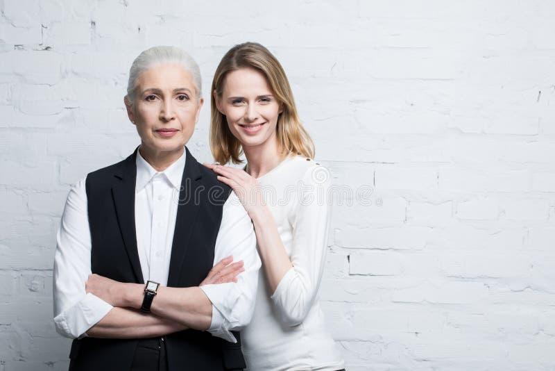 站立美丽的微笑的妇女一起,年轻和资深人民 免版税库存图片