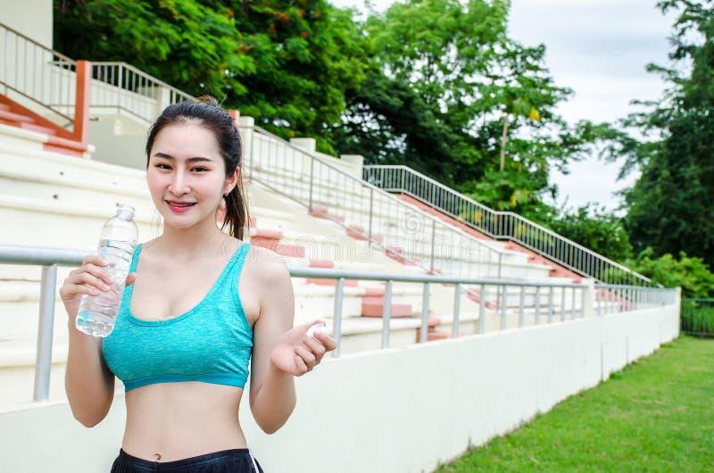 站立美丽的母的赛跑者射击户外拿着水瓶 休假的健身妇女在连续锻炼以后 库存图片