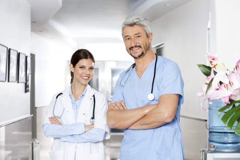 站立胳膊的确信的男性和女性生理治疗师横渡 免版税图库摄影