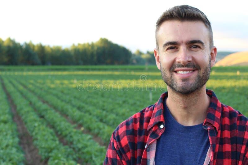 站立英俊的农夫骄傲和满意微笑 图库摄影