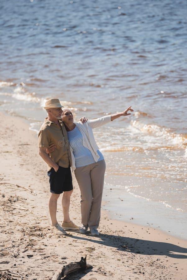 站立资深的夫妇拥抱在沙滩和看  图库摄影