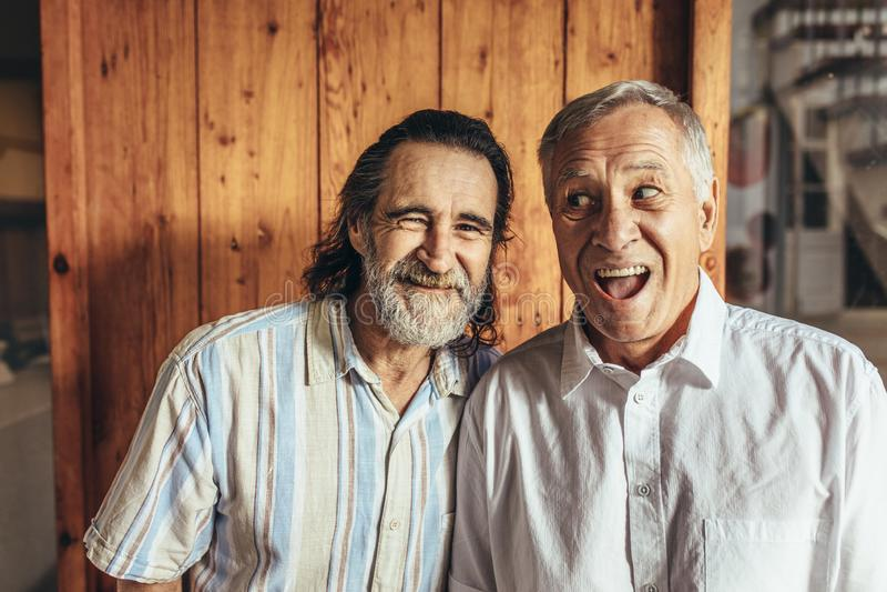 站立资深的朋友一起做滑稽的面孔 免版税库存照片