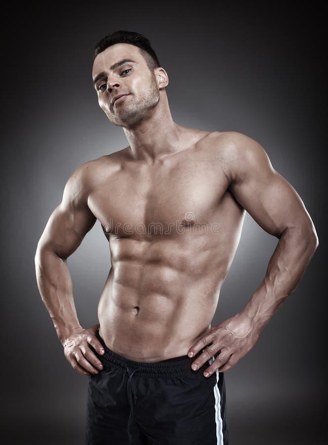 站立赤裸上身的运动的人两手插腰 库存图片