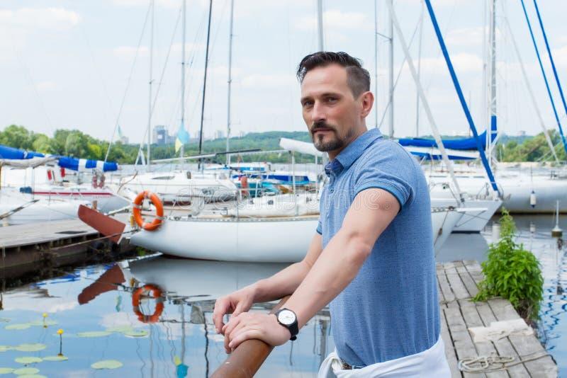 站立近与小船的码头障碍的驾游艇者 看对的有胡子的人在旅途近游艇前 免版税图库摄影