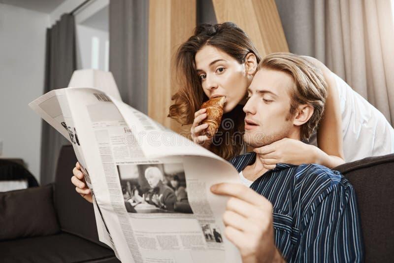 站立近的丈夫的可爱的逗人喜爱的妻子读他的报纸和吃新月形面包,当拥抱他从后面时 库存图片
