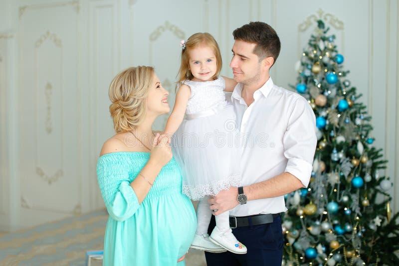 站立近的丈夫的怀孕的欧洲妇女保留小女儿在圣诞树附近 免版税库存照片