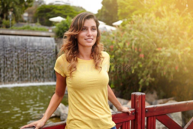 站立近的公园瀑布的沉思少妇 免版税图库摄影