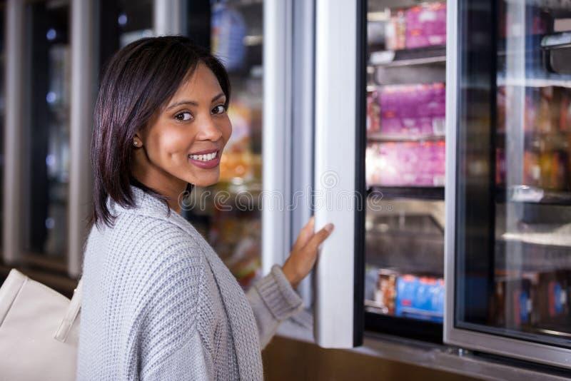 站立近的冰箱的妇女 库存图片
