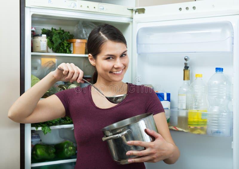 站立近的冰箱的饥饿的浅黑肤色的男人 免版税库存照片