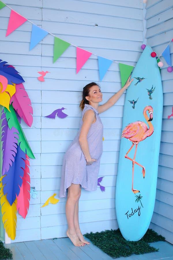 站立近的冲浪板和装饰的儿童房子的年轻白种人孕妇 库存图片