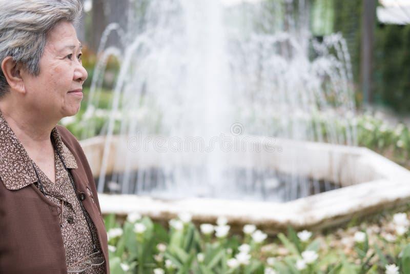 站立近的喷泉的亚裔老妇人在庭院里 年长seni 免版税库存照片