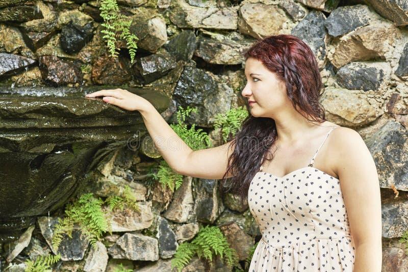 站立近的喷泉的女孩 免版税库存照片