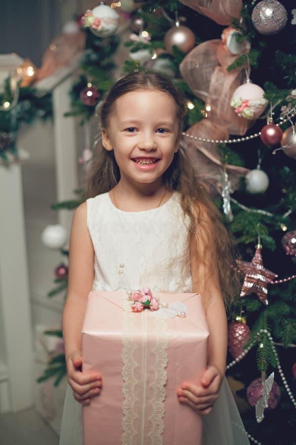 站立近的圣诞树和拿着礼物的礼服的女孩 免版税图库摄影