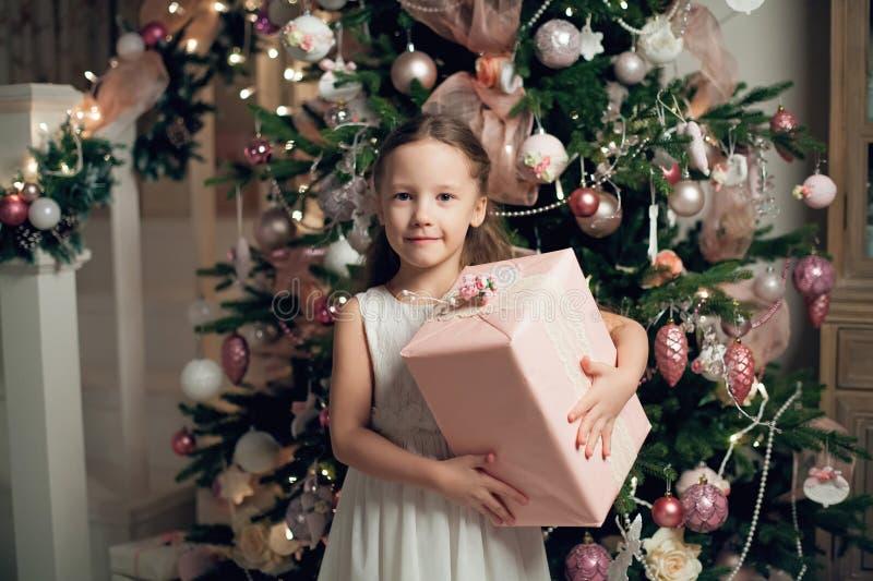 站立近的圣诞树和拿着礼物的礼服的女孩 库存照片