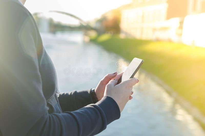 站立近的城市河的女孩,当拿着手机时 库存照片