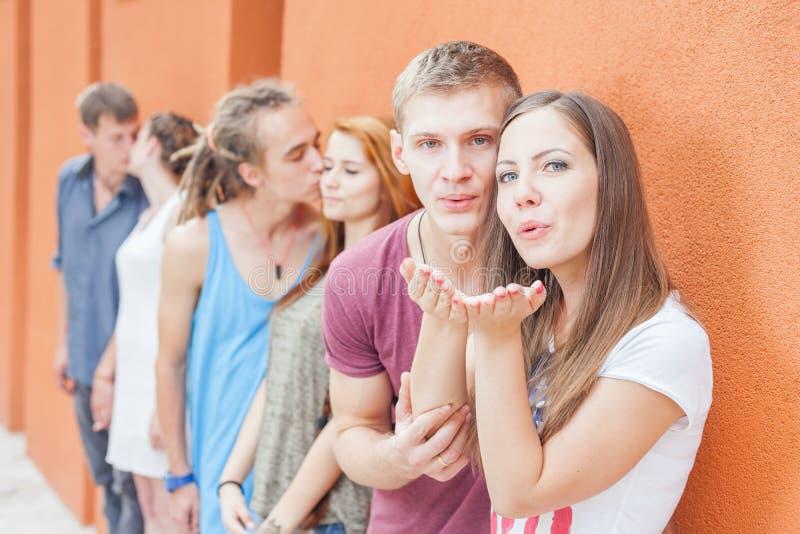 站立近的墙壁和亲吻的小组愉快的青年人 库存图片