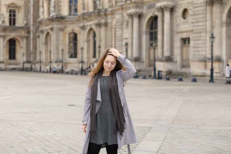 站立近的天窗有软的焦点背景,巴黎的灰色外套的俏丽的妇女 免版税库存图片