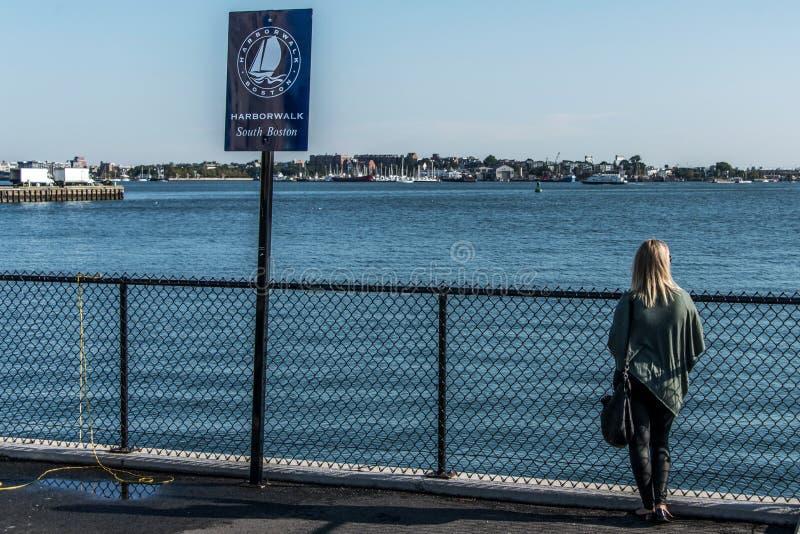 站立近的岗位标志波士顿港口全景步行的女孩游人隔绝在一个晴朗的夏日久的码头 免版税库存图片