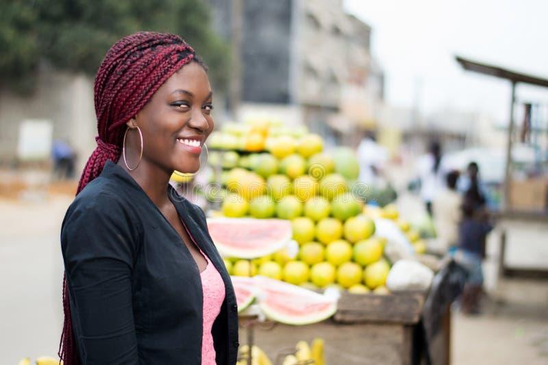 站立近的果子的微笑的少妇画象搁置 免版税图库摄影