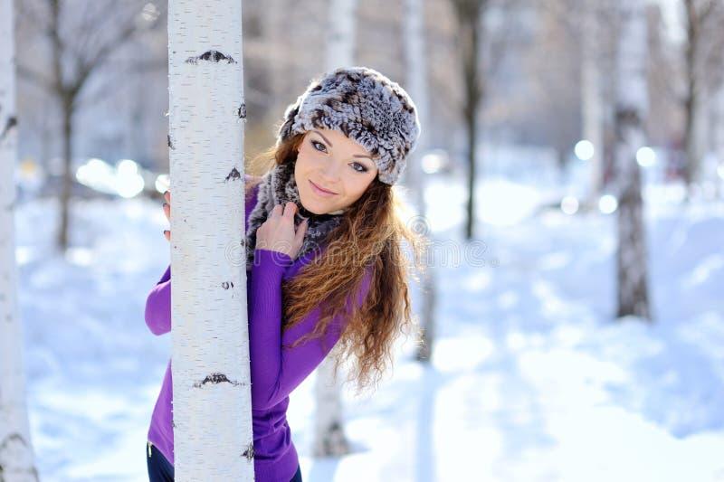 站立近的桦树的美丽的女孩在冬天公园 免版税图库摄影
