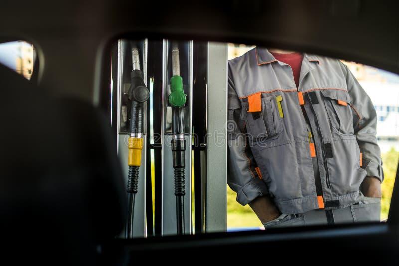 站立近的燃料驻地泵浦,看法的加油站工作者通过车窗 免版税库存照片