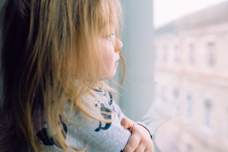 站立近的窗口和看的小女孩 免版税库存照片