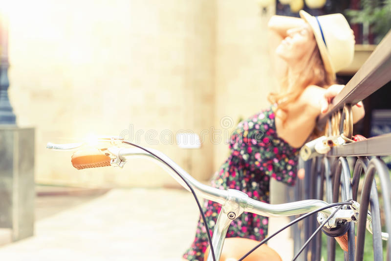 站立近的篱芭的女孩,在葡萄酒城市自行车附近 库存照片