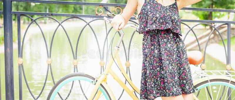 站立近的篱芭的女孩,在葡萄酒城市自行车附近 免版税图库摄影