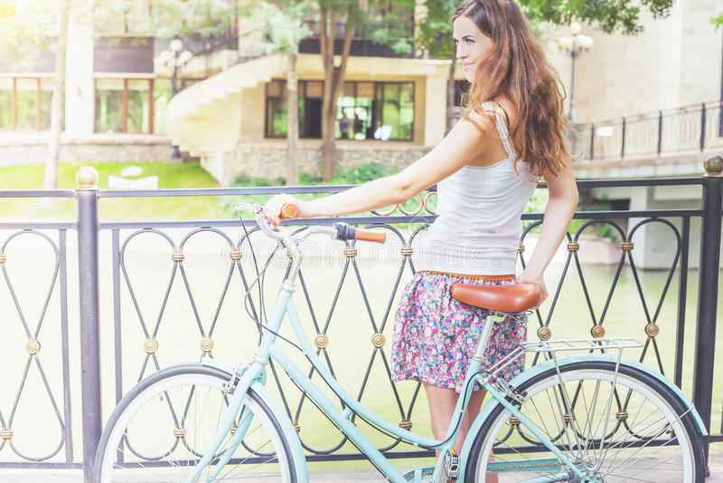 站立近的篱芭的女孩,在葡萄酒城市自行车附近 免版税库存图片