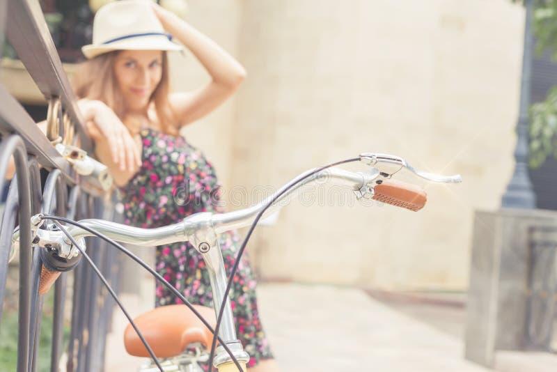 站立近的篱芭的女孩,在葡萄酒城市自行车附近 库存图片