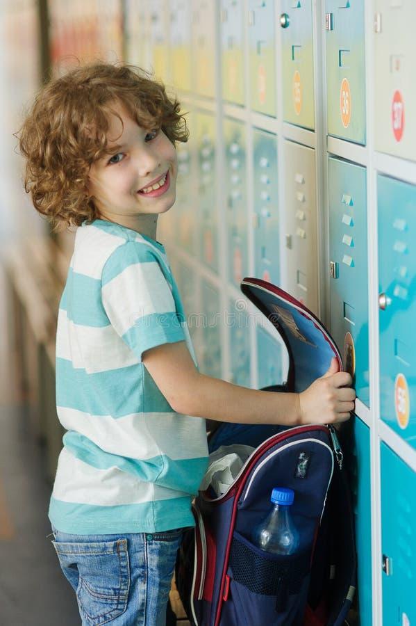 站立近的衣物柜的小学学生在走廊 免版税库存图片