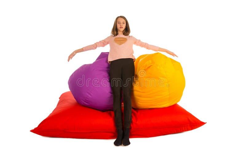 站立近的装豆子小布袋椅子和装豆子小布袋沙发的女孩 免版税库存照片