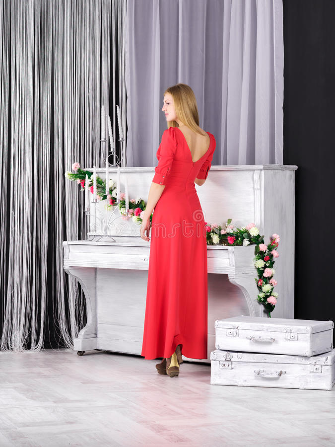 站立近的钢琴的红色礼服的女孩 库存图片