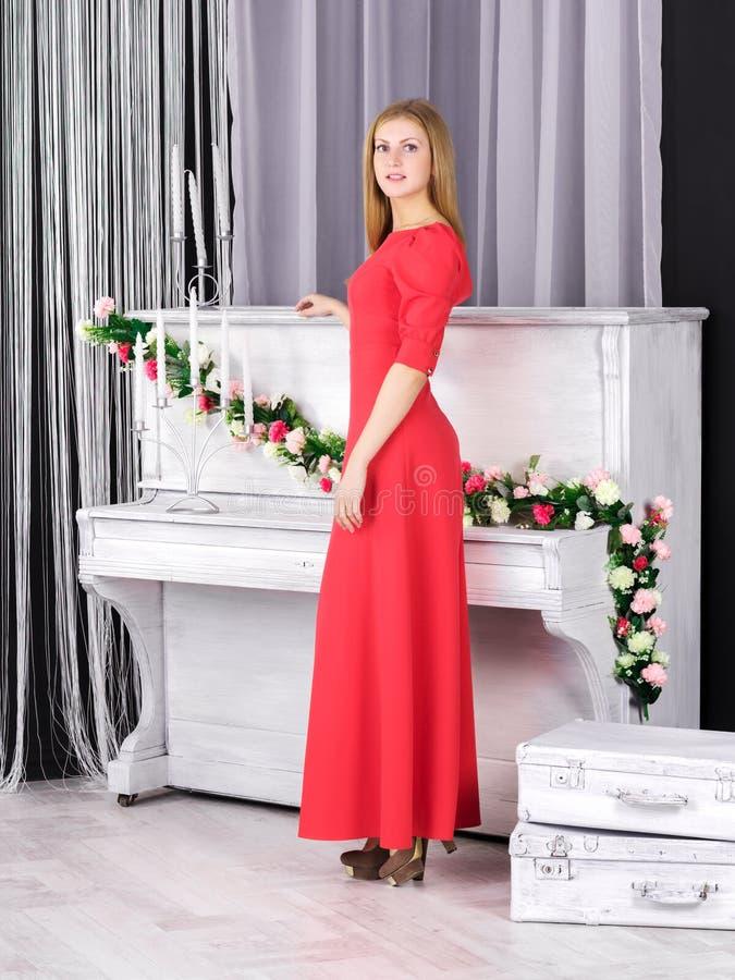 站立近的钢琴的红色礼服的女孩 免版税图库摄影