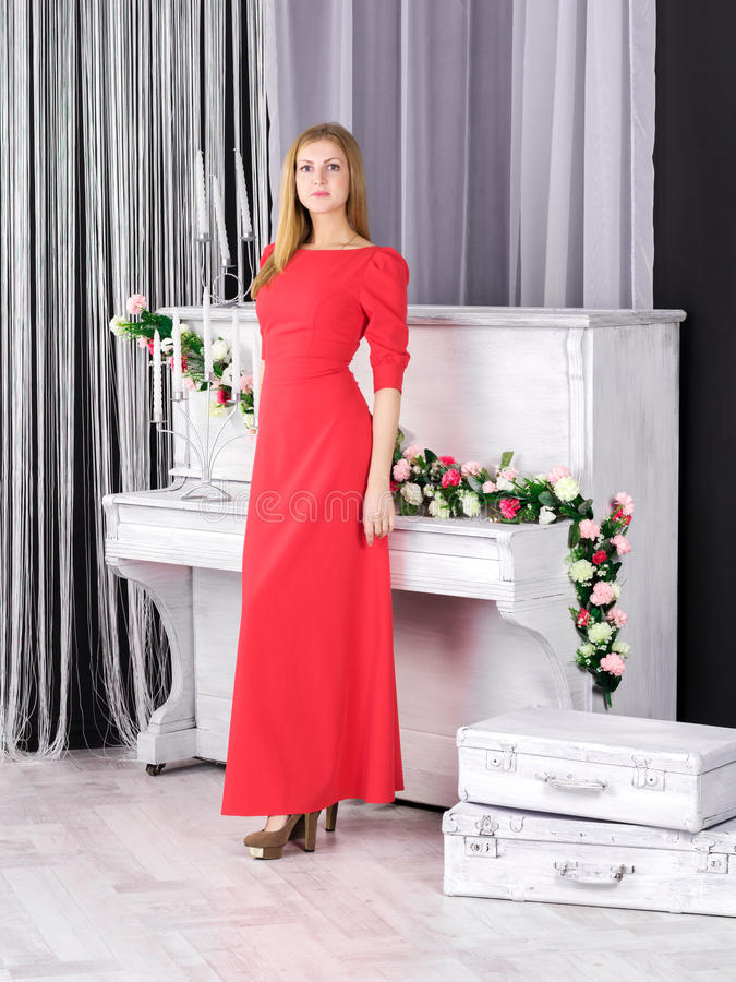 站立近的钢琴的红色礼服的女孩 免版税库存图片