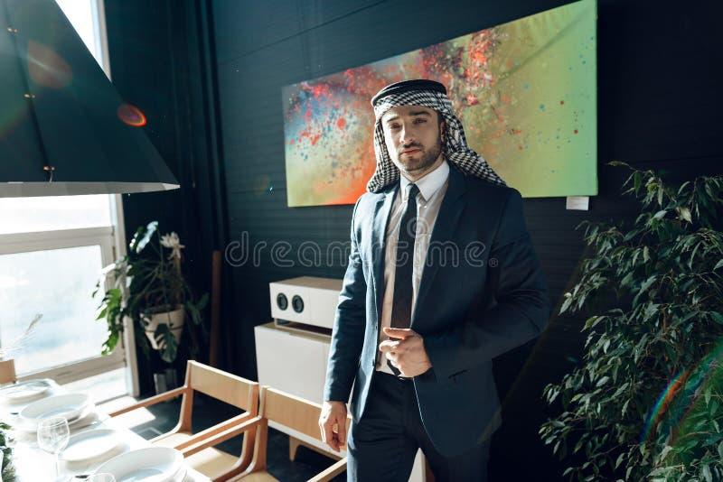 站立近的饭桌的阿拉伯商人在旅馆客房 图库摄影