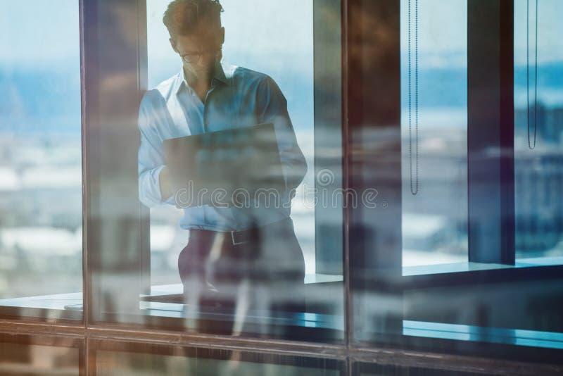 站立里面办公楼和使用膝上型计算机的商人 库存照片
