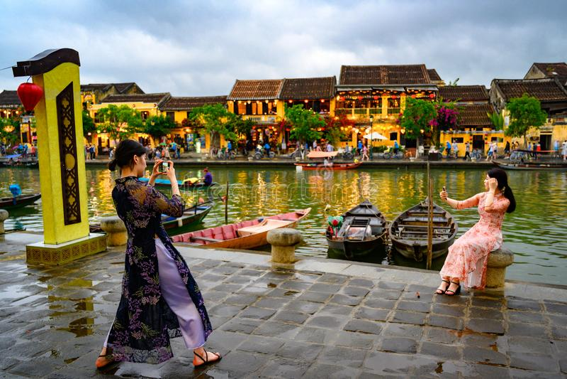 站立除大众观光业外在运河的另一边在旅游目的地会安市的,越南妇女在会安市,越南