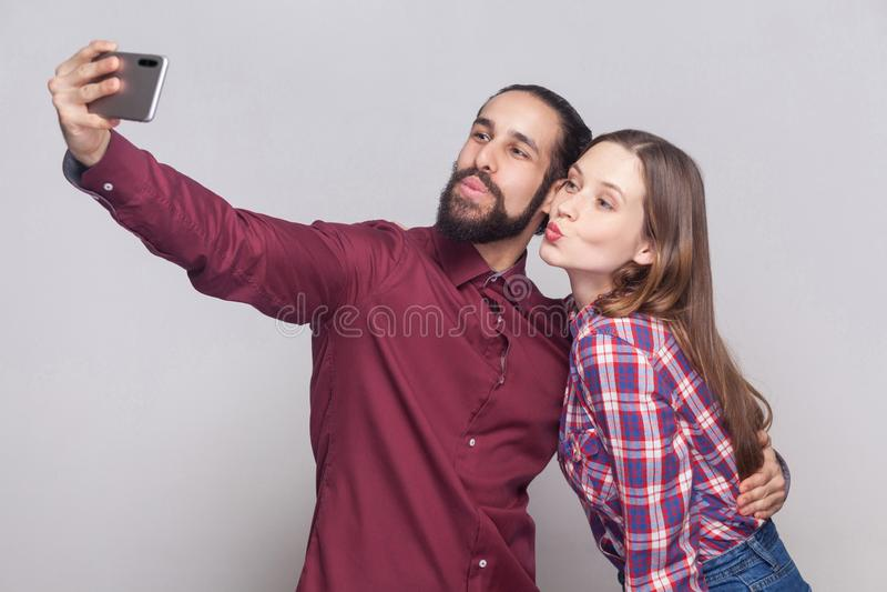 站立,看和亲吻流动智能手机照相机的愉快的夫妇画象打selfie或视频通话 免版税库存图片