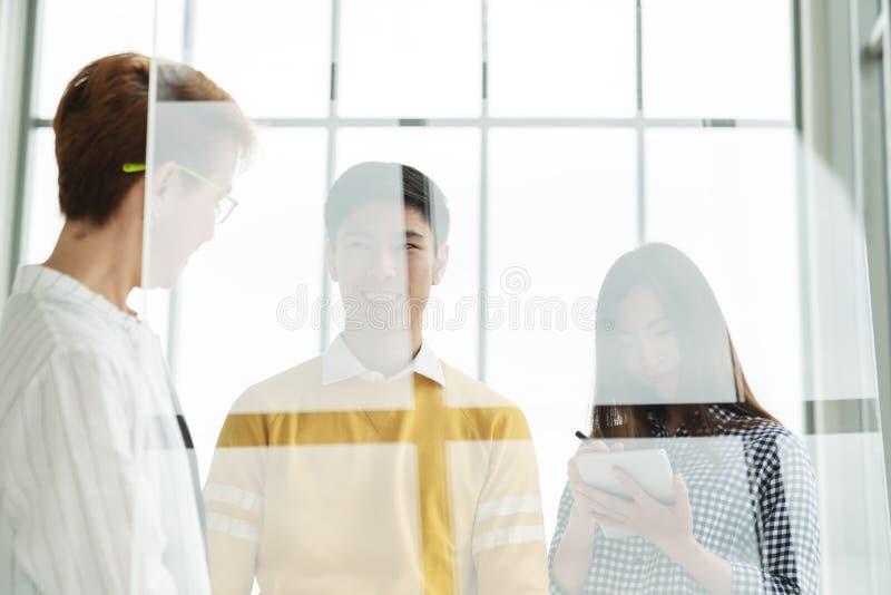 站立,谈话和听会见的小组年轻亚裔可爱的商人在透明玻璃w后的经理 库存图片