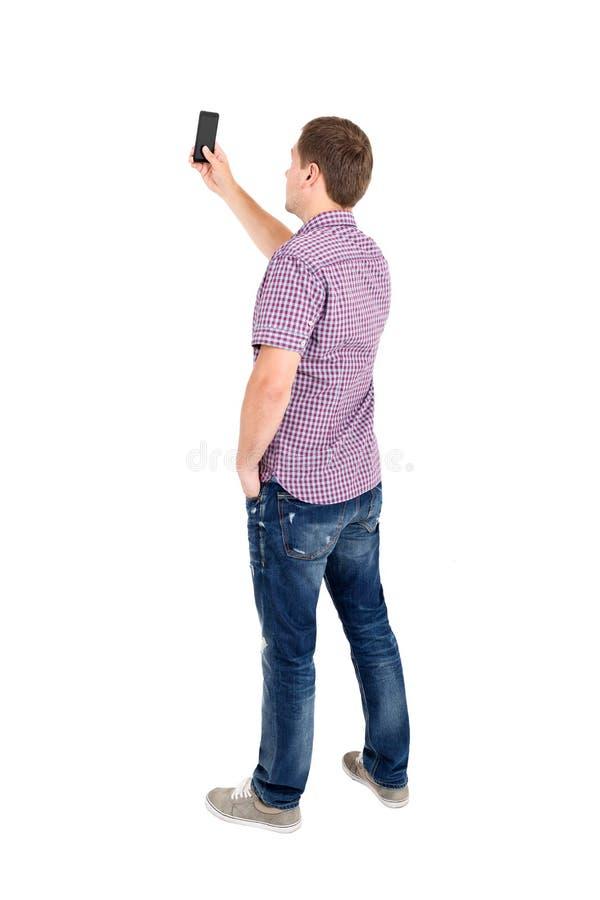 站立年轻人和使用一个手机后面看法  免版税库存图片
