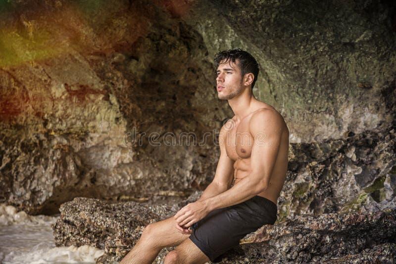 站立年轻的人赤裸上身,小山在背景中 免版税库存照片