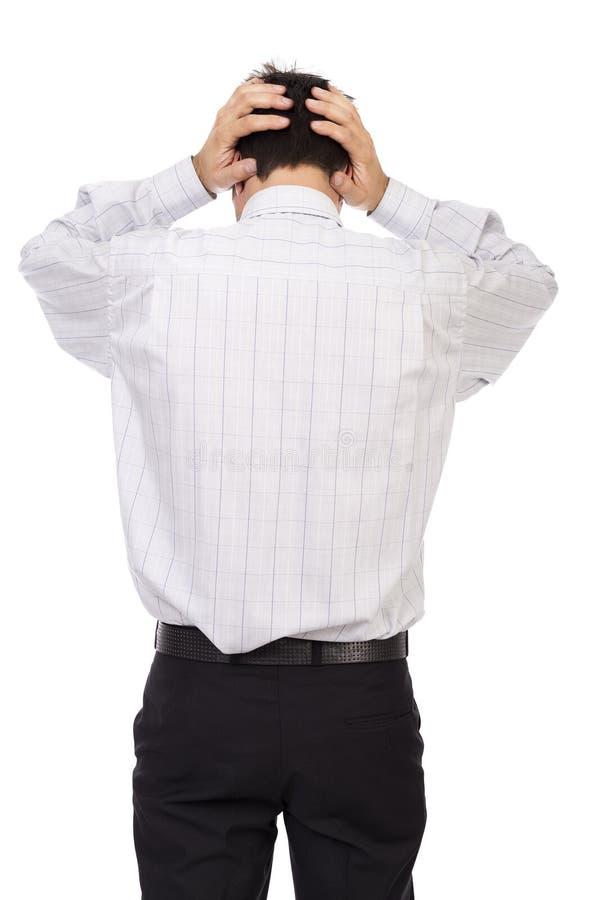 站立年轻的商人阻挡在头的手 免版税库存照片