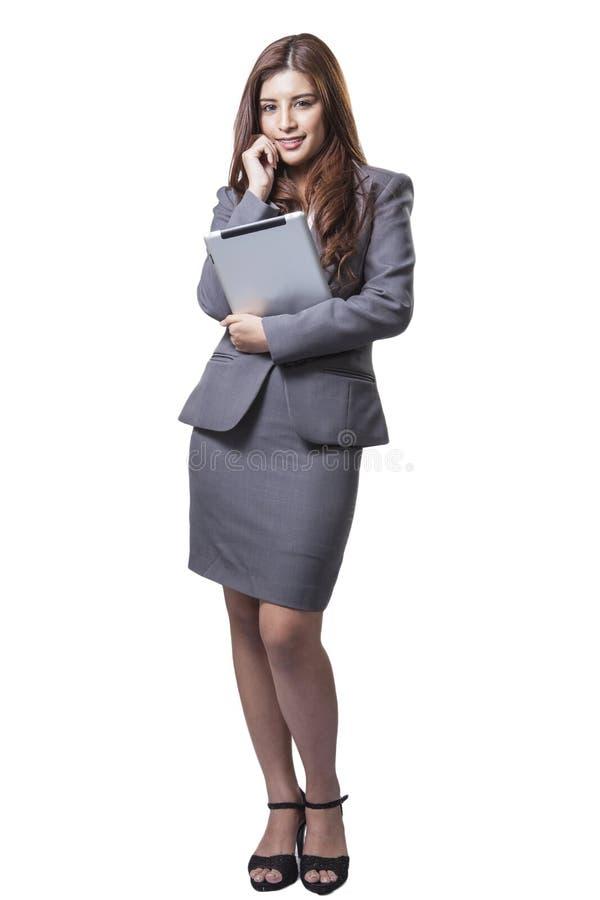 站立年轻的女实业家拿着数字式片剂 库存照片