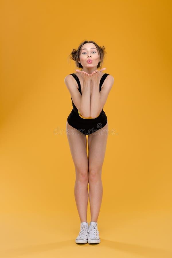 站立黑的泳装的可爱的逗人喜爱的少妇送亲吻 图库摄影