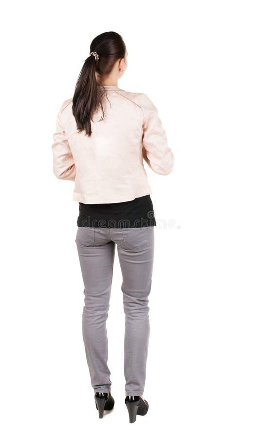 站立年轻美丽的深色的妇女后面看法 免版税库存照片
